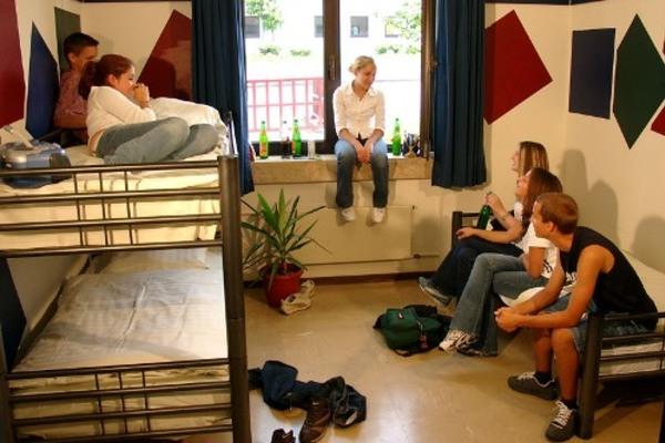 Jugendliche sitzen gemeinsam im Zimmer